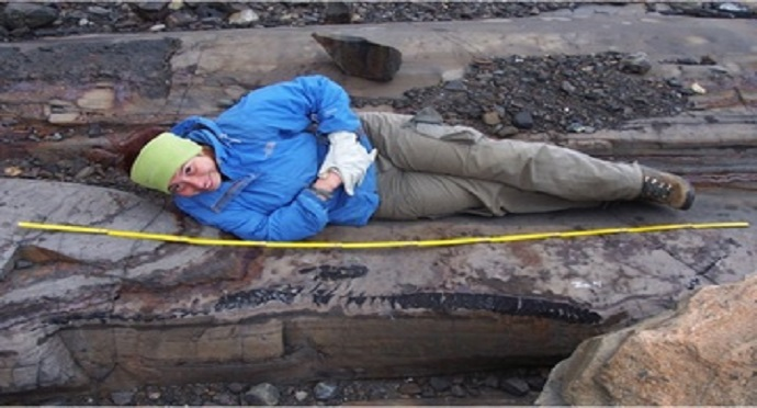 An archaeologist lies next to 'ichthyosaur' remains in Chile's Torres del Paine National Park. Photo by @TomJohnsonJr / Twitter.